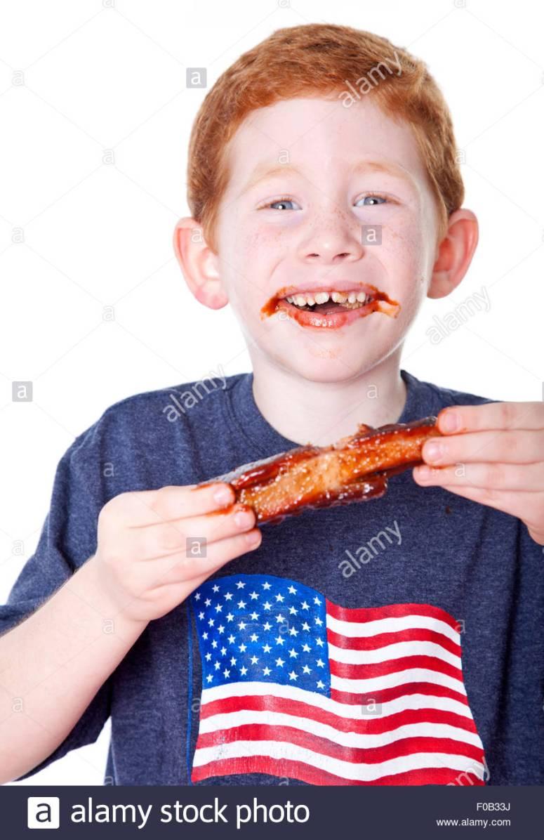 hungry-boy-eating-bbq-rib-in-studio-F0B33J.jpg